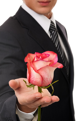 Young business man hold rose. Isolated on white